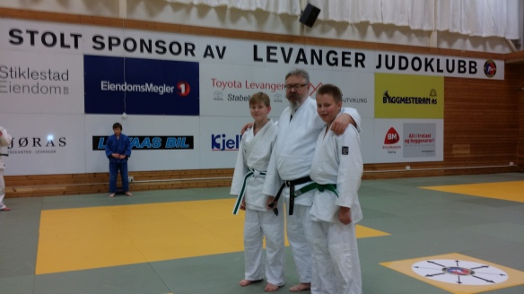 Grønt belte til Mathias Eriksen (t.v.) og Ole Øystein Venås, sammen med sensor Alf Birger Rostad.