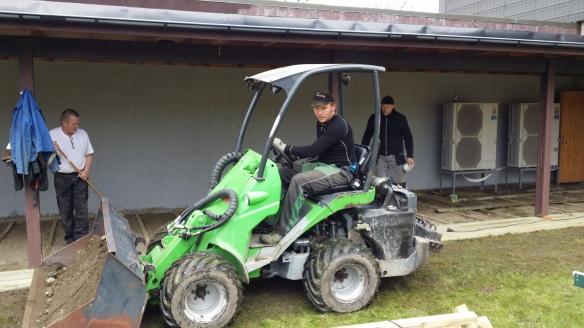 """Tor-Erik Ertzaas var primus motor for bygging av platting på """"grillplassen"""". Her på en mini-hjullaster mens Thor Holbø og Egil Kvåle jobber med muskelkraft."""